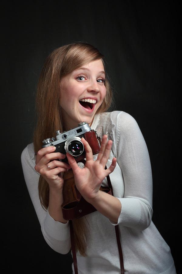 She does like cameras   camera, black background, smile, white shirt
