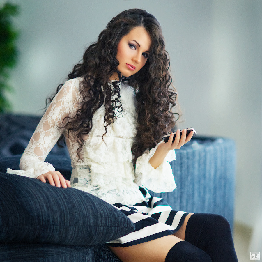 Pretty girl with curly hair on the sofa | portrait, girl, pretty, brunette  , hair, curly, blouse, gaiters, skirt, mobile phone