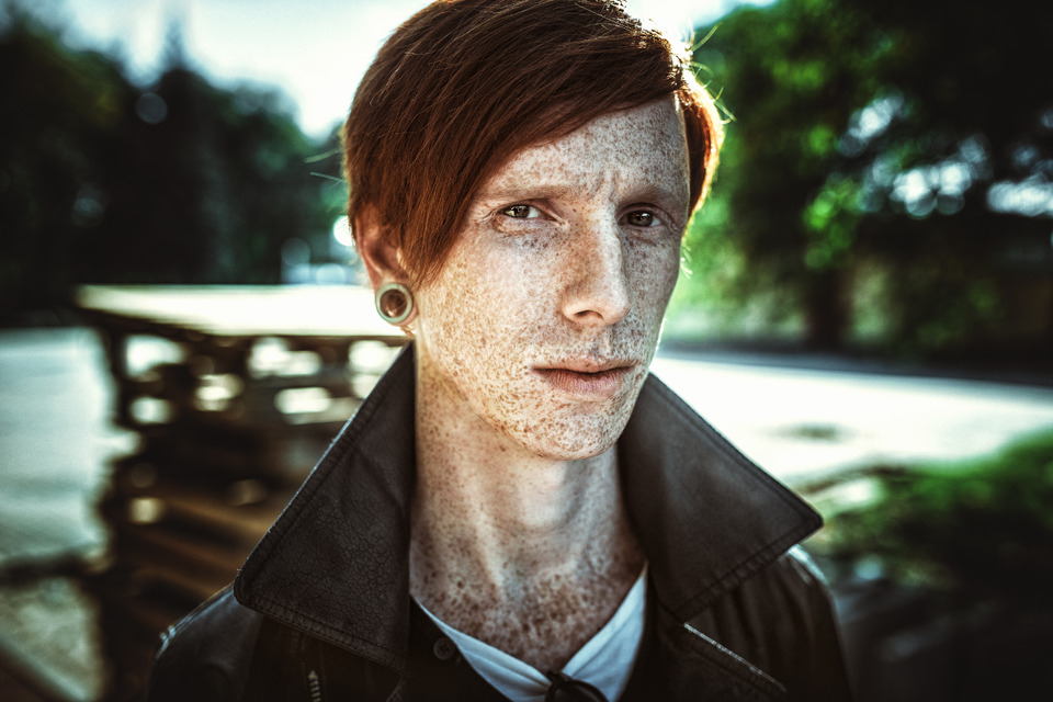 Freckled redhead man with ear tunnels | ear tunnel, freckled model, redhead man, environmental portrait, trees, light