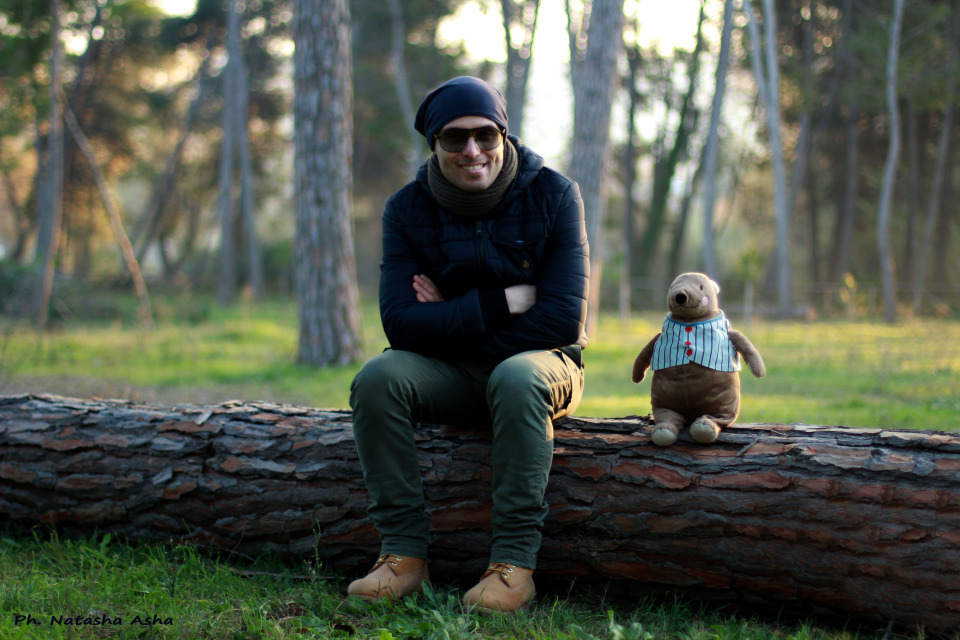 Man and teddy bear sitting on the log | portrait, model, man, forest, trees, teddy bear, sun glasses, smile, green grass, log